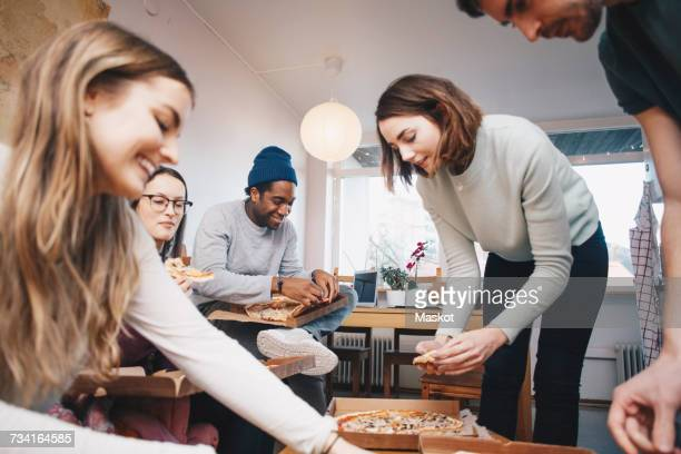 Happy young friends eating pizza in college dorm room