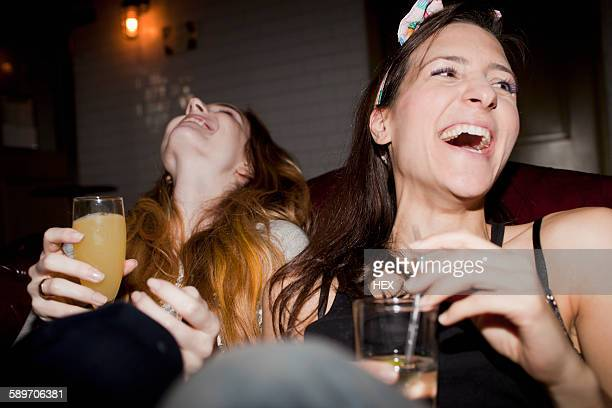 happy young friends enjoying drinks at a bar - ladies' night stock pictures, royalty-free photos & images