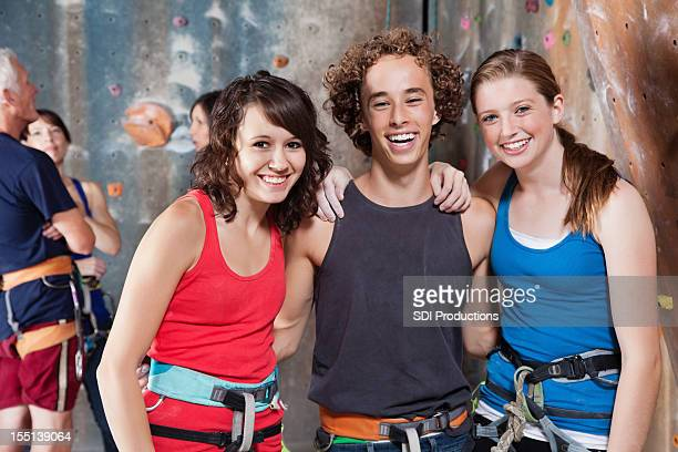 Happy young friends enjoying time at the rock climbing gym