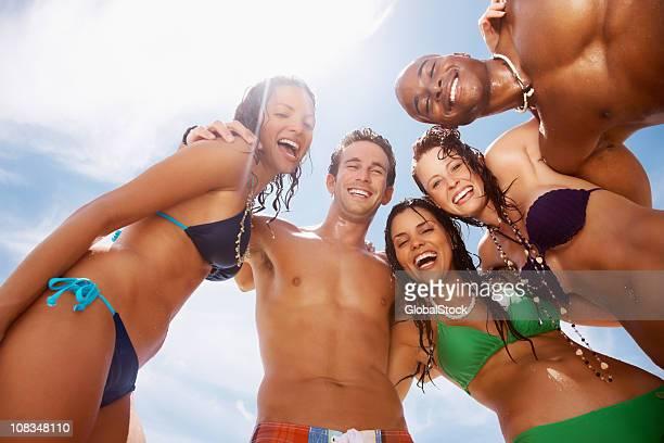 Glückliche junge Freunde, die zusammen am Strand gegen Himmel