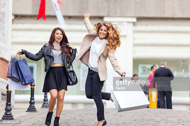 Happy young friends jumping with shopping bags