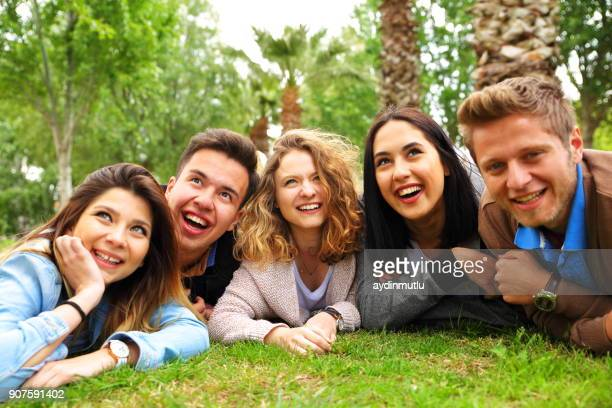 happy young friends lying in the park - creole ethnicity stock pictures, royalty-free photos & images