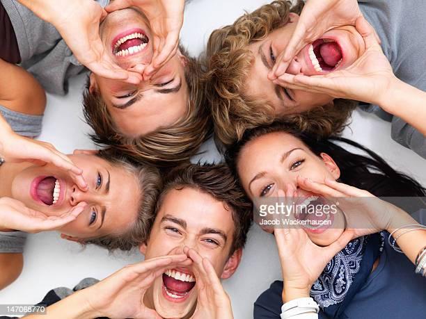 Glückliche junge Freunde zusammen schreien und liegen