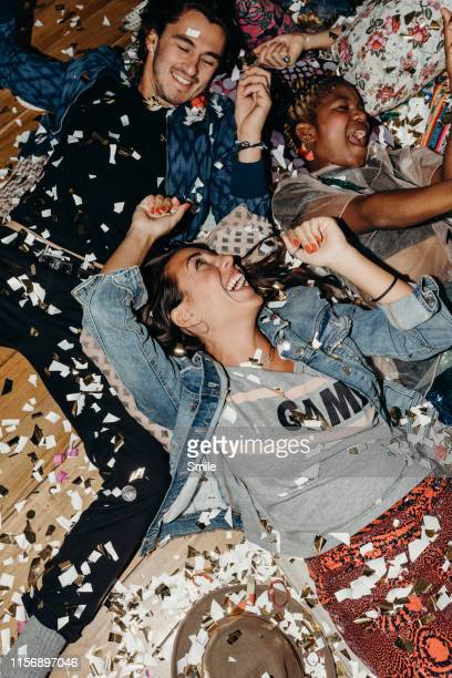 happy young friends on cushions and confetti on the floor - after party stock-fotos und bilder