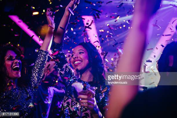 Happy young friends partying with drinks and confetti in nightclub