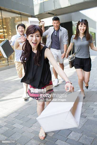 Happy young friends running with shopping bags