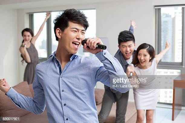Happy young friends singing and dancing in living room