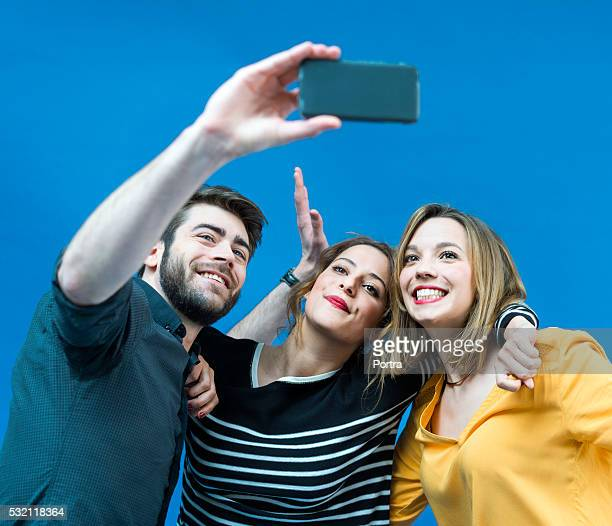 Happy young friends taking selfie from smartphone against blue screen