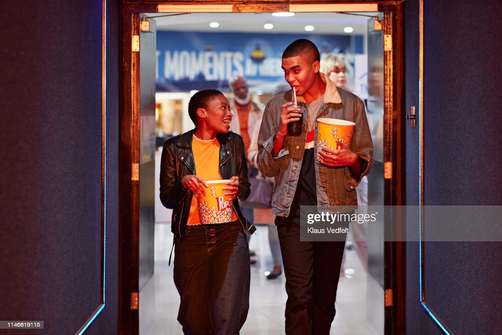Happy young friends talking while walking in corridor at movie theater : Stock Photo