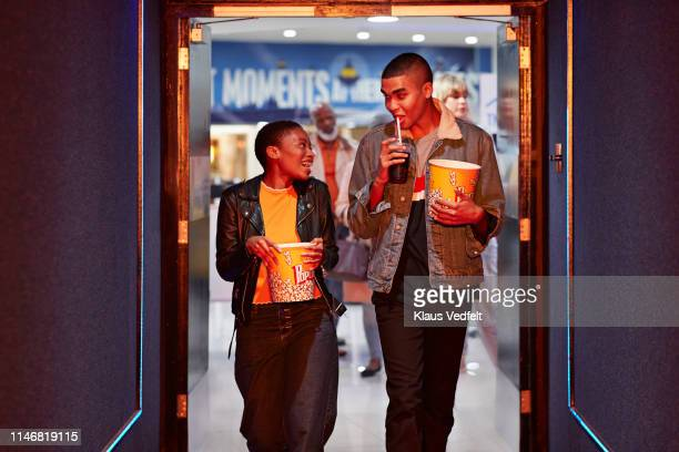 happy young friends talking while walking in corridor at movie theater - daten stockfoto's en -beelden