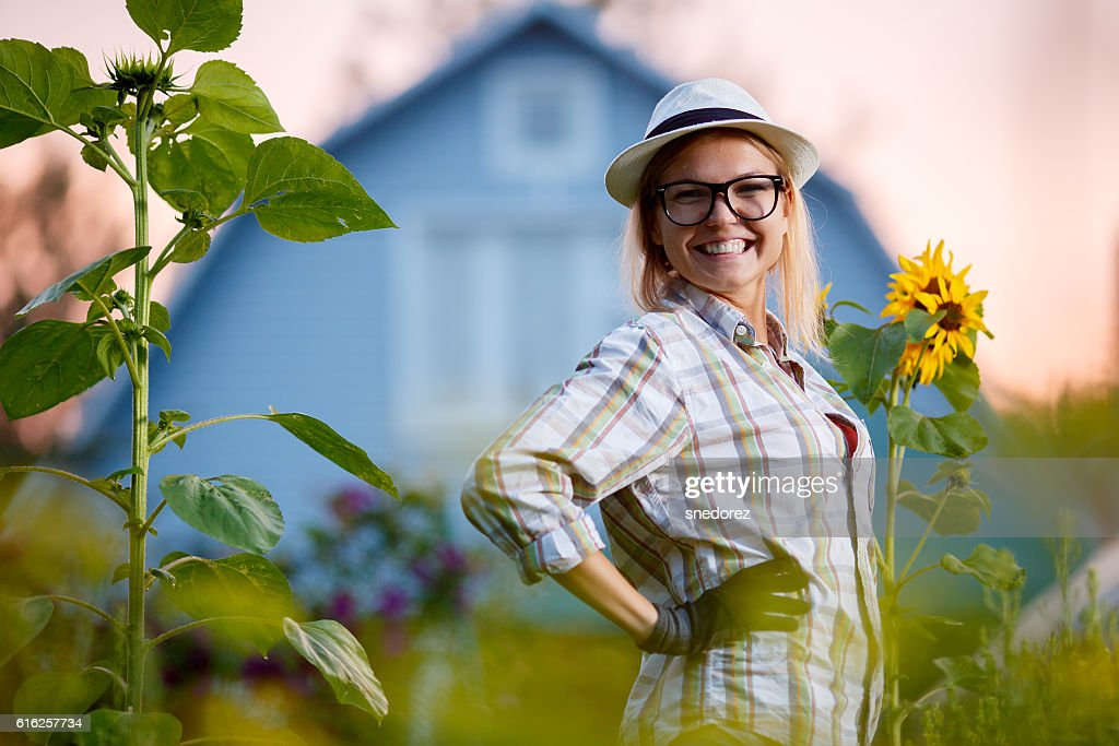 Happy young gardener posing in garden before her cottage : Stock Photo