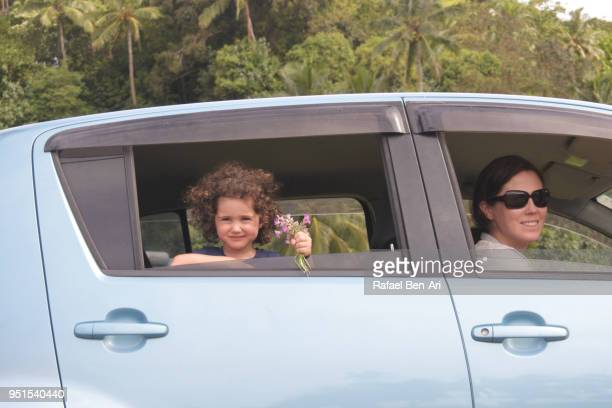 happy young girl and her mother looking out of a car window during a road trip in rarotonga cook islands - rafael ben ari fotografías e imágenes de stock