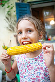 happy young girl eating corn outdoors
