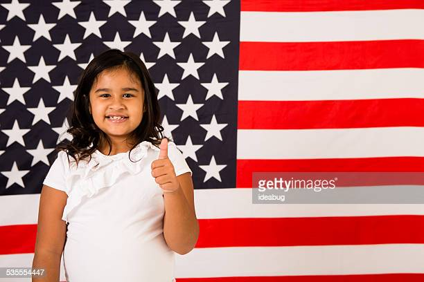 Happy, Young Girl Giving Thumbs Up by American Flag