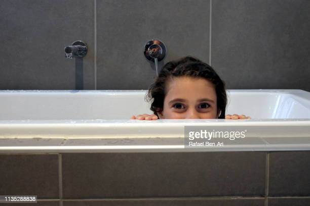 Happy young girl having a bath