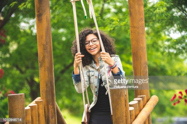 Happy young girl having fun on the swing