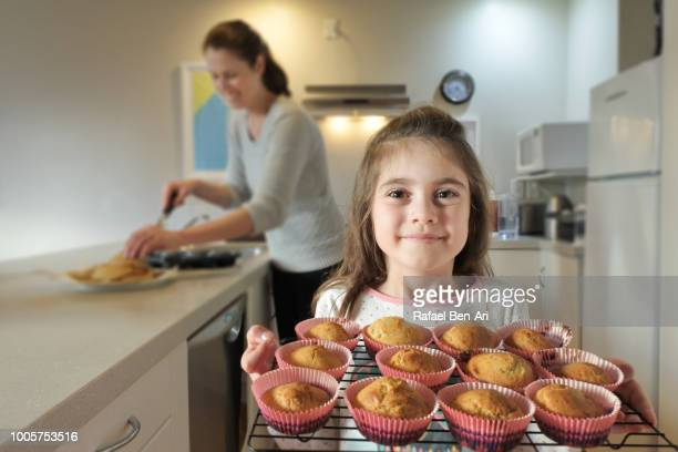 happy young girl helping her mother to bake muffins. - rafael ben ari stock pictures, royalty-free photos & images