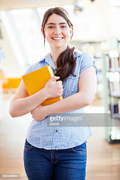 Happy young girl holding a book at library