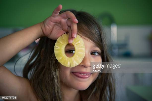 happy young girl holding a pineapple slice - pineapple stock pictures, royalty-free photos & images