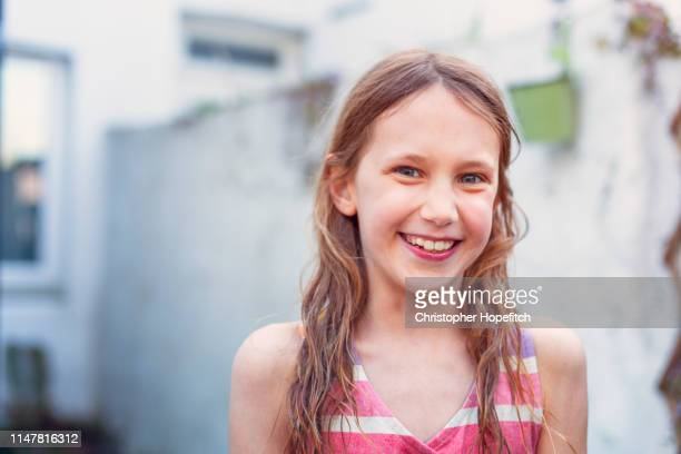 happy young girl in garden smiling at camera - girls stock pictures, royalty-free photos & images