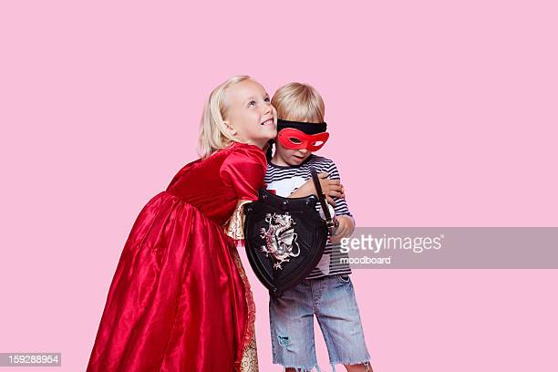 Happy young girl in princess costume hugging boy pretending to be her hero over pink background