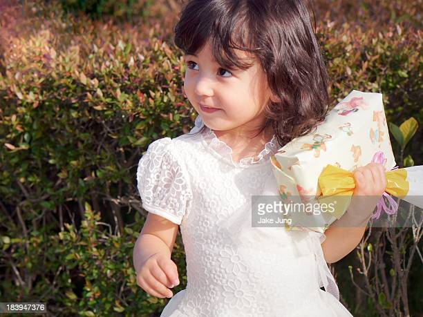 Happy young girl in white dress holding present