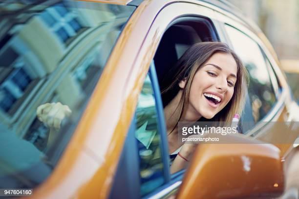 fröhliches junges mädchen setzt lippenstift in den stau - vehicle mirror stock-fotos und bilder
