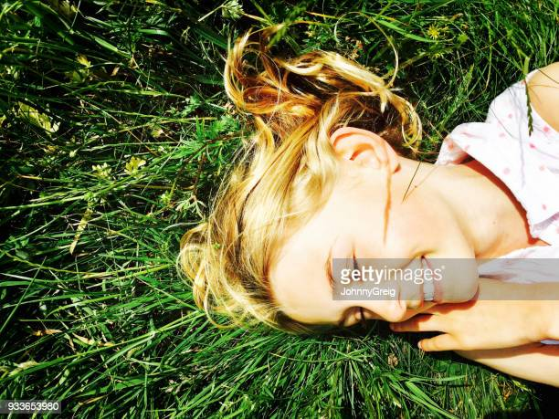 Happy young girl lying in summer grass smiling