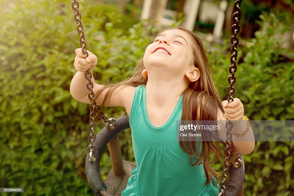 Happy young girl on a swing : Stock Photo
