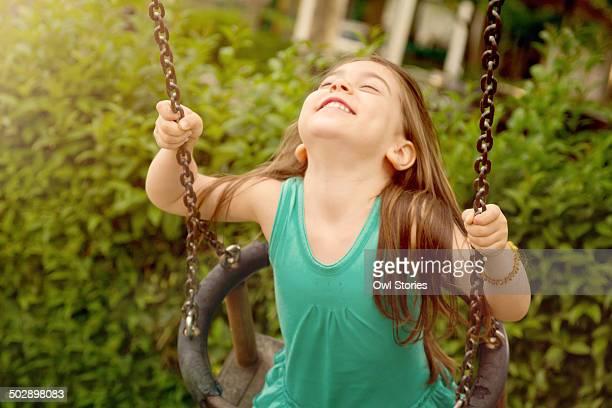happy young girl on a swing - cabeza hacia atrás fotografías e imágenes de stock