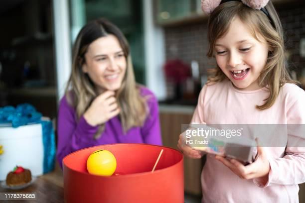 glückliches junges mädchen öffnen ein geschenk zu hause - kindertag stock-fotos und bilder