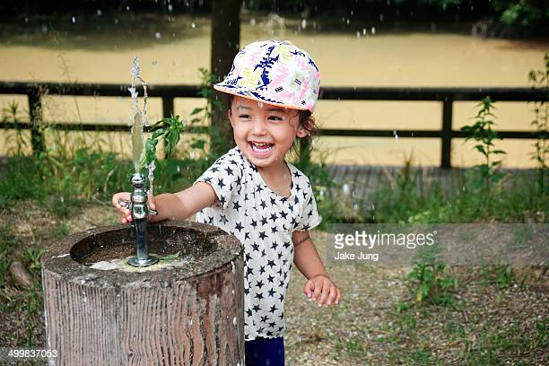 Happy young girl playing with park water fountain