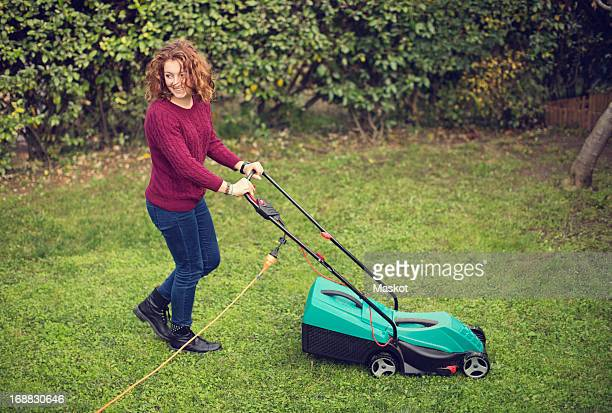 Happy young girl pushing electric lawn mower on grass