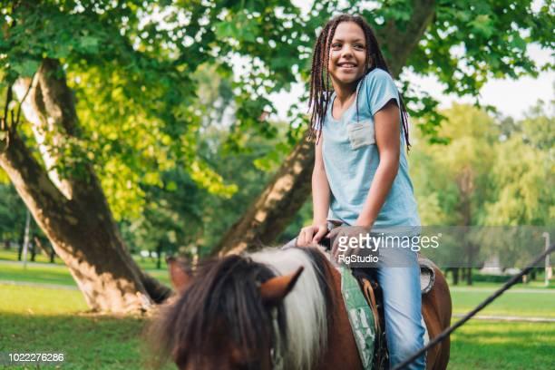 glad ung tjej rider en häst - pony play bildbanksfoton och bilder