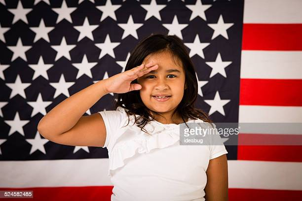 Happy, Young Girl Saluting in Front of American Flag