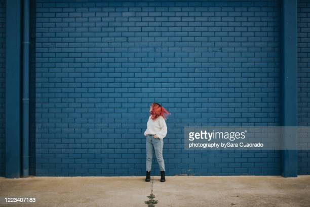 happy young girl shaking her hair in front of blue brick wall - brick wall stock pictures, royalty-free photos & images