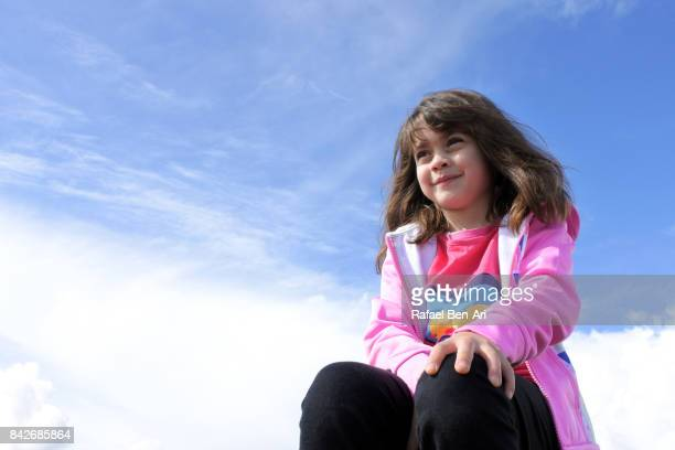 Happy young girl sits under blue sky