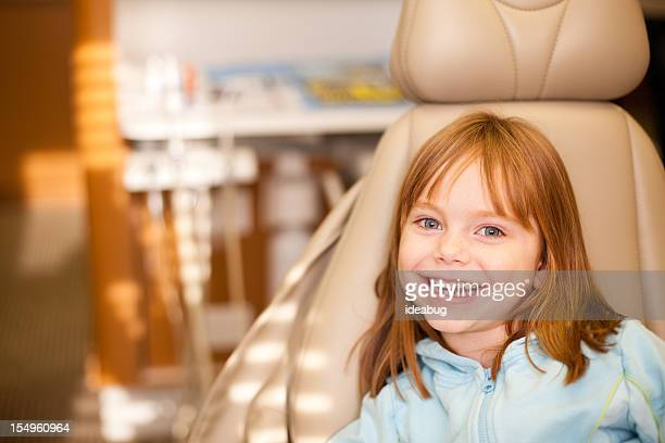 Happy Young Girl Sitting in Dental Chair at Dentist Office