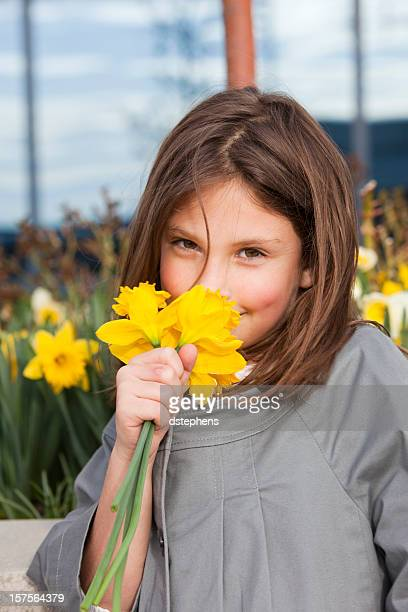 happy young girl smelling daffodils - daffodils stock photos and pictures