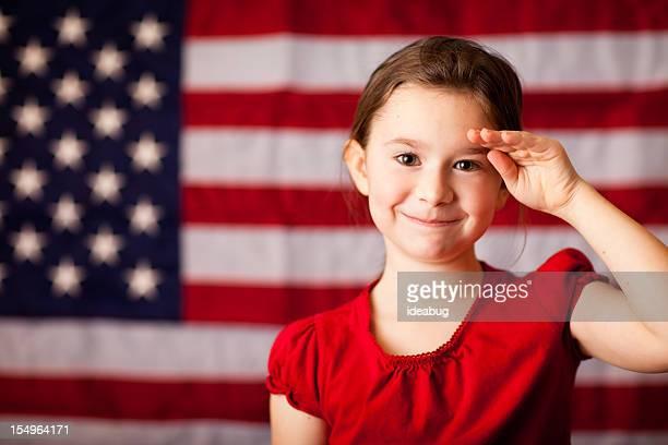幸せな、若い少女の笑顔と敬礼、アメリカの国旗