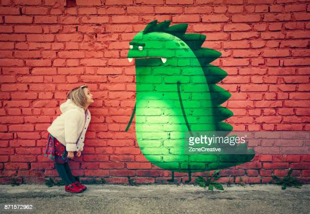 happy young girl smiling to imaginary monster friend painted on outdoor wall - murale foto e immagini stock