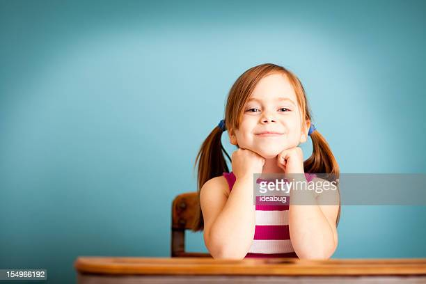 Happy Young Girl Student Sitting in School Desk