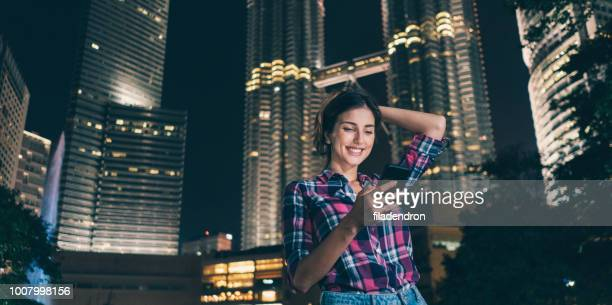 happy young girl texting outdoor in the night - baby mobile stock photos and pictures