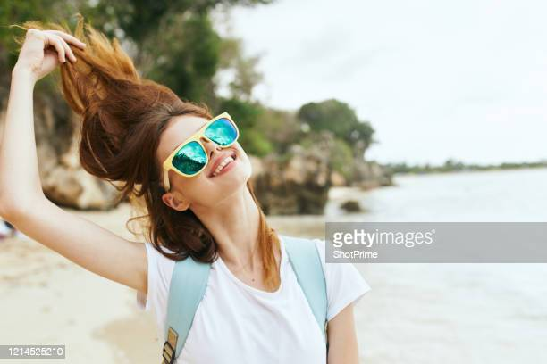 a happy young girl with a large backpack behind her walks along the beach of a tropical island. - lagoon stock pictures, royalty-free photos & images