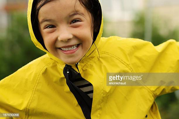 Happy young girl with a rain coat