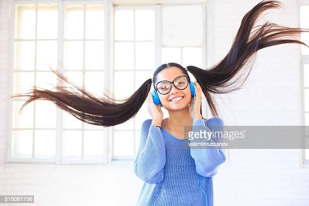 Happy young girl with blue headphones jumping