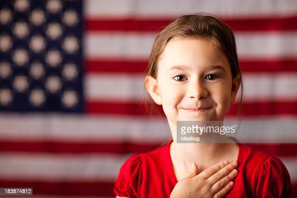 Happy Young Girl with Hand on Heart by American Flag