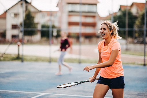 Happy young girls playing tennis 1015444322