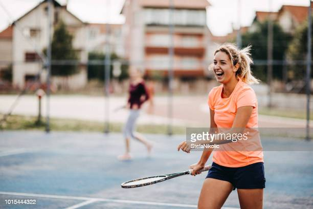 happy young girls playing tennis - doubles stock photos and pictures