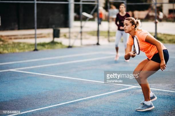ragazze felici che giocano a tennis - doppio foto e immagini stock